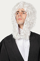 Young man dressed as judge looking away over gray background