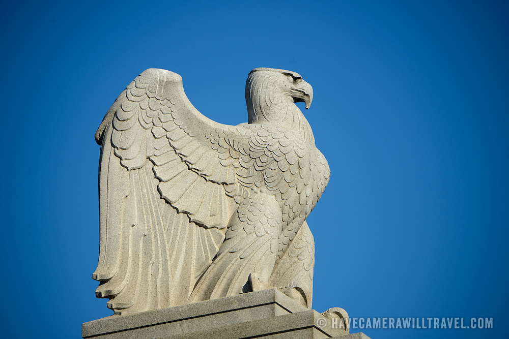 A large statue of an eagle stands guard over the entrance road to Arlington Cemetery.