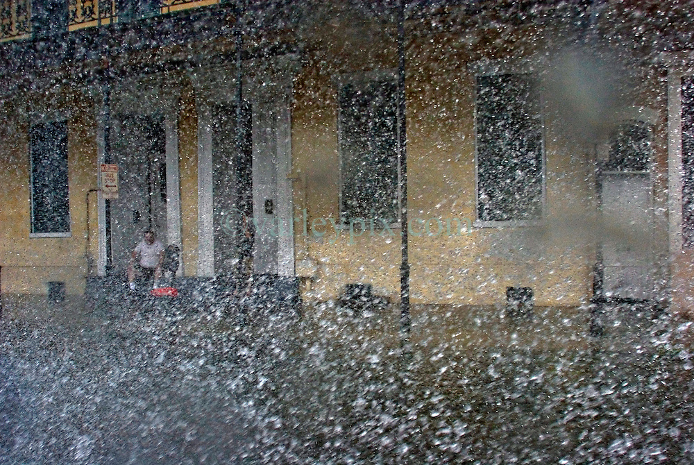 29 August, 2005. New Orleans, Louisiana.<br /> Hurricane Katrina hits New Orleans. A man sits on his stoop in the French Quarter as the storm lashes the city.<br /> Photo; Charlie Varley.