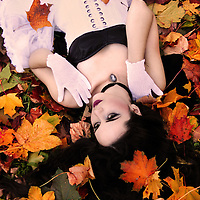 A girl with pale skin and long black hair, dressed in a white corset dress lying in colorful fallen autumn leaves.