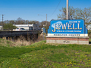 """26 APRIL 2020 - JEWELL, IOWA: The highway going into Jewell, a small community in central Iowa that became a food desert when the only grocery store in town closed in 2019. The grocery store served four communities within a 20 mile radius of Jewell. Some of the town's residents are trying to reopen the store, they are selling shares to form a co-op, and they hold regular fund raisers. Sunday, they served 550 """"grab and go"""" pork roast dinners. They charged a free will donation for the dinners. Despite the state wide restriction on large gatherings because of the COVID-19 pandemic, the event drew hundreds of people, who stayed in their cars while volunteers wearing masks collected money and brought food out to them. Organizers say they've raised about $180,000 of their $225,000 goal and they hope to open the new grocery store before summer.      PHOTO BY JACK KURTZ"""