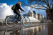 cyclist on a Swapfiets in front of the Chocolate Museum at the river Rhine, puddle, Cologne, Germany.<br /> <br /> Radfahrerin auf einem Swapfiets vor dem Schokoladenmuseum am Rhein, Pfuetze, Koeln, Deutschland.