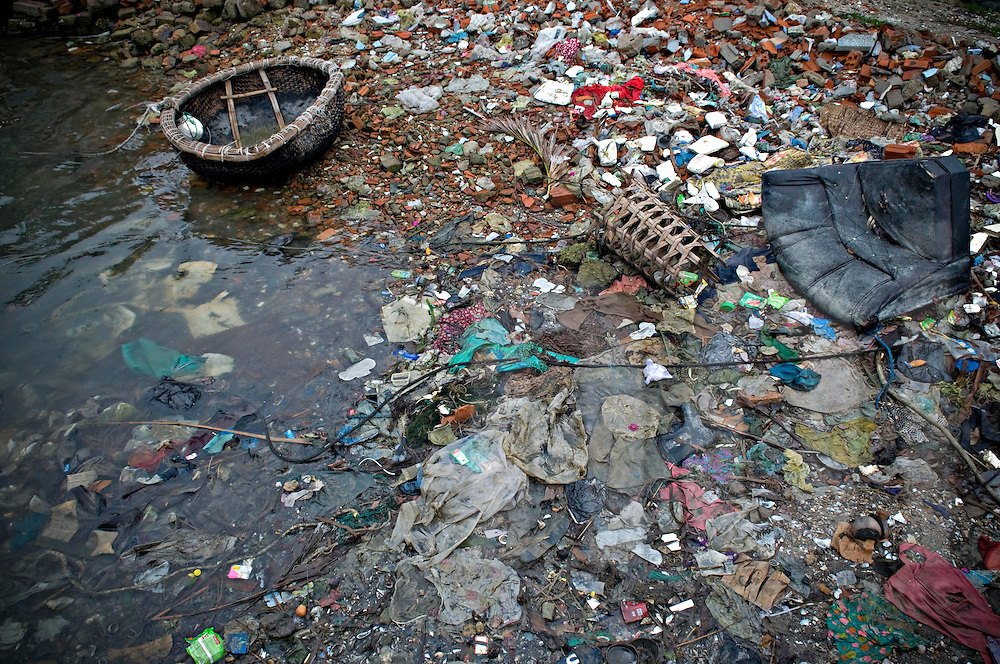Dramatic polluted area close to a river in Khanh Hoa province, Vietnam, Asia. Ground is full of plastic bags and various rubbish while the water tends to be blackish.
