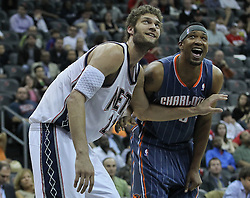 Apr 11; Newark, NJ, USA; New Jersey Nets center Brook Lopez (11) and Charlotte Bobcats center Kwame Brown (54) joke around during the second half at the Prudential Center. The Bobcats defeated the Nets 105-103.