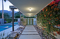 Tiled foothpath leading to door of modern house