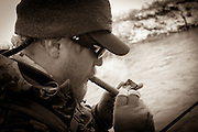 Fly Angler Mike Schmidt of Angler's Choice Flies, takes a break from fishing to light a cigar.