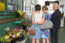 © Licensed to London News Pictures. 07/07/2015. London, UK. People look at floral tributes shortly before observing a minute silence at Aldgate tube station in London, on the tenth anniversary, for victims of the 7/7 bombings. Photo credit : Vickie Flores/LNP
