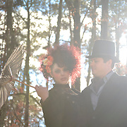 A woman with red hair holding an umbrella and a man wearing a top hat stand in the evening sun for their Tim Burton-style engagement portrait session in Pittsboro, NC.