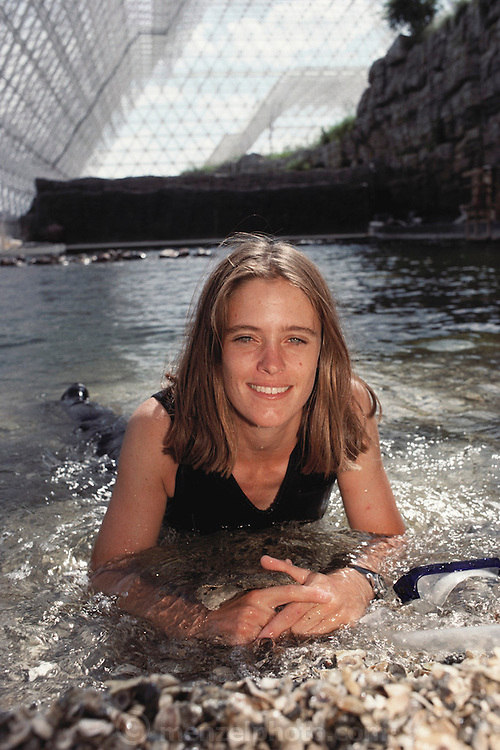 Biosphere 2 Project undertaken by Space Biosphere Ventures, a private ecological research firm funded by Edward P. Bass of Texas.  Biosphere scientist Abigail Alling seen in the artificial ocean of the Biosphere 2 Project during construction. The Ocean 'biome' provided a source of fish during the two-year duration of the Project. Water that evaporated from the surface of the 'ocean' was condensed and filtered to provide fresh water for consumption and to replenish the freshwater stream.  Biosphere 2 was a privately funded experiment, designed to investigate the way in which humans interact with a small self-sufficient ecological environment, and to look at possibilities for future planetary colonization. 1990