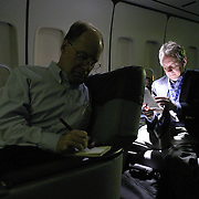 Reuters White House correspondent Steve Holland and Associated Press White House correspondent Terry Hunt (under light) go over notes in the press cabin as Air Force One flies enroute to Baghdad International Airport Thursday, November 27, 2003.  In a clandestine night time move President Bush, with the knowledge of only a handful of senior staff, departed his ranch in Crawford, Texas and flew through the night to spend the Thanksgiving Day holiday visiting troops stationed in the war torn country...Photo by Khue Bui