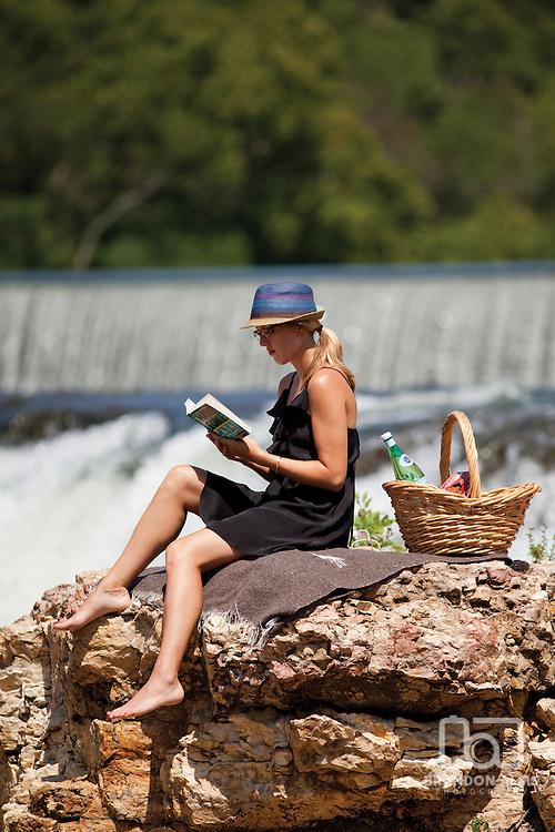 A woman reads a book on a rock in Grand Falls located in Joplin, Missouri.