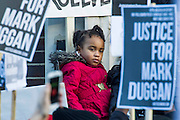 """Supporters of Mark Duggan's family hold a vigil outside Tottenham  police station. They gathered, alongside family members and his mother Pam Duggan, at 2pm following an inquest jury ruling that Duggan was lawfully killed when police shot him dead while he was unarmed.  Within days of his shooting, in 2011, rioting broke out on the streets of London, and spread to other urban areas in England.  Pastor Nims Obunge, who oversaw Duggan's funeral in 2011, said: """"The message from the family is that this vigil is intended to be a very peaceful vigil"""". Tottenham, London, UK 11 January 2014. Guy Bell, 07771 786236, guy@gbphotos.com"""