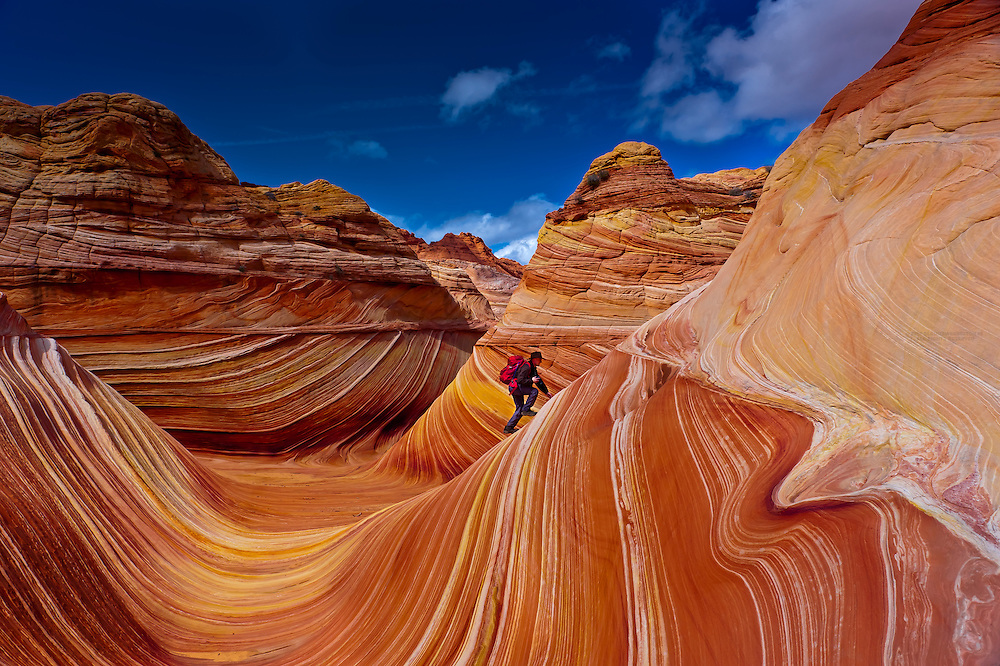 "Hiker exploring ""The Wave"", a 190 million year old Jurassic-age Navajo sandstone rock formation, Coyote Buttes, Paria Canyon-Vermillion Cliffs Wilderness Area, Utah-Arizona border, USA"