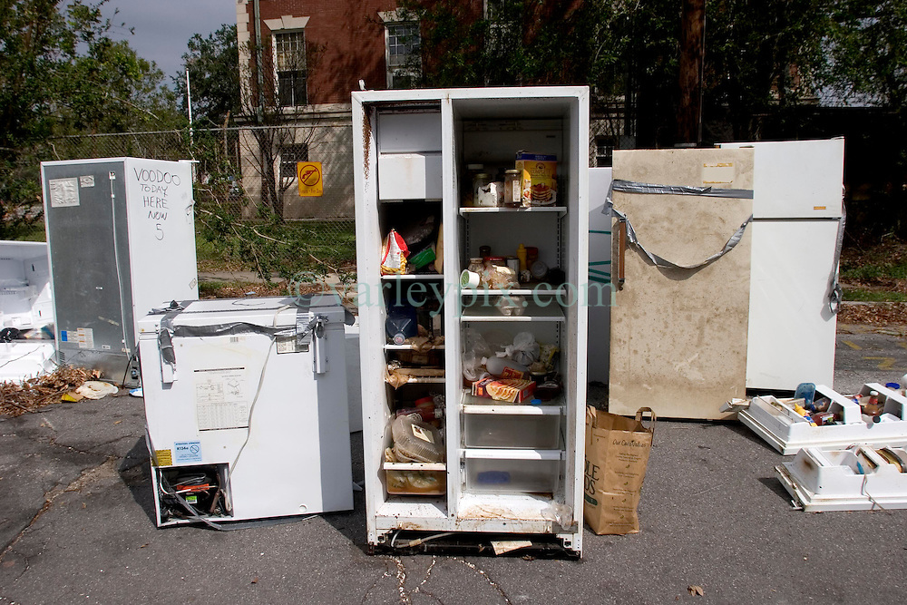 09 Oct, 2005.  New Orleans, Louisiana. Hurricane Katrina aftermath.<br /> Refrigerator line the sidewalks and streets of Uptown neighbourhoods as residents return and throw away the fetid, stinking appliances. Many are taped shut to prevent them from opening. Someone has written, 'Voodoo here today now 5,' on many of the appliances.<br /> Photo; ©Charlie Varley/varleypix.com