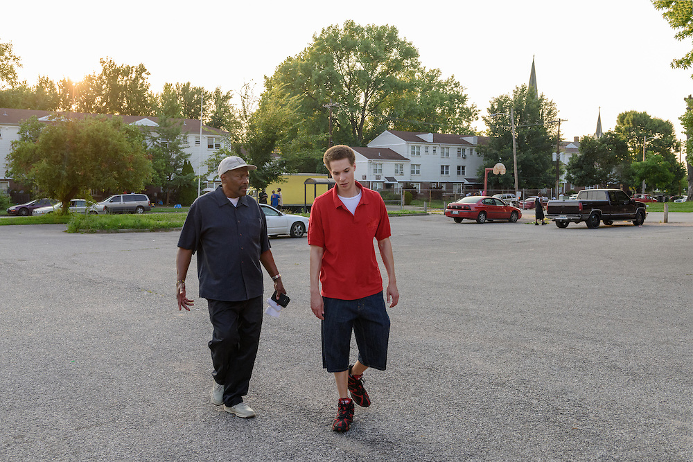 Eddie Woods, director of Street Peace: No More Red Dots, left, talks with his son Darin Woods, Monday, June 20, 2016 on the walk back to the car in front of the Baxter Community Center in the Beecher Terrace neighborhood. (Photo by Brian Bohannon)