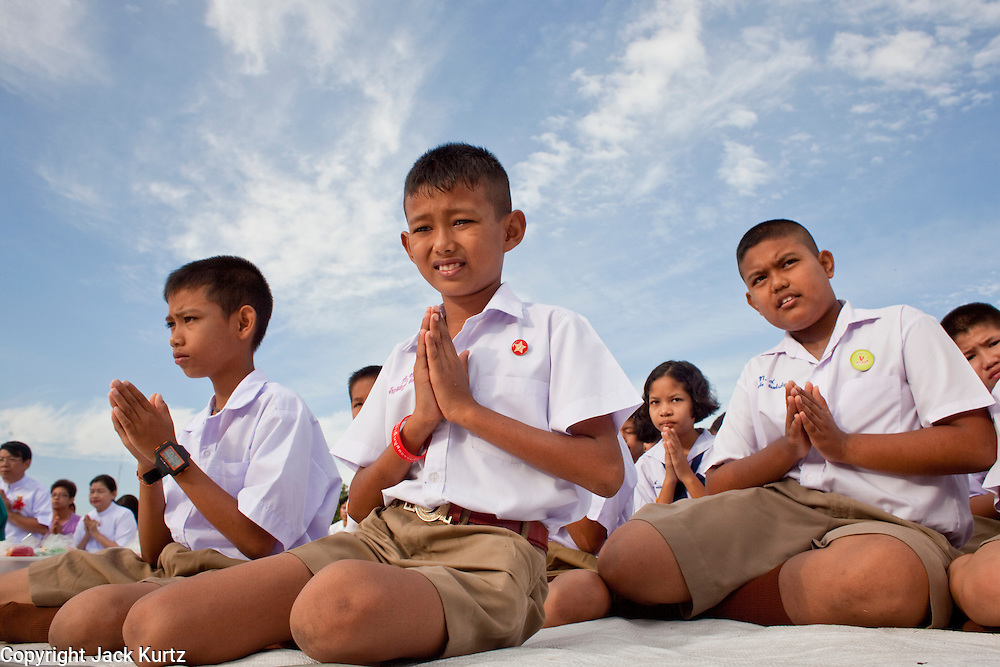 "Sept. 26, 2009 -- PATTANI, THAILAND: Thai school children pray during the Tak Bat Sankatan ceremony in Pattani, Thailand, Saturday. Buddhists in Thailand's three southern most provinces gathered in Pattani Saturday, Sept 26 to celebrate Tak Bat Sankatan, the day Lord Buddha returned to earth and was greeted by a crawd of his disciples and Buddhist believers who were waiting to offer him food. Buddhists monks representing the 266 ""Wats"" (temples) in the three provinces (Pattani, Narathiwat and Yala) processed through the crowd and were presented with food and gifts.   Photo by Jack Kurtz"