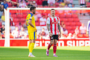 Chris Maguire (#7) of Sunderland AFC smiles at Luke O'Neill (#2) of AFC Wimbledon after scoring the second goal for Sunderland during the EFL Sky Bet League 1 match between Sunderland and AFC Wimbledon at the Stadium Of Light, Sunderland, England on 24 August 2019.
