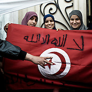 "Some Muslims girls show a Tunisian flag  ""There is only Allah"" written at the top of it. Currently in Tunisia there is a tensional and dangerous.situation among the two Islamic parties: Ennhadda and Al Nhadda, both not admitted during Ben Ali regime. Al Nhadda and Ennhadda are candidates for the forthcoming elections of the 24th of July 20011 but women, and especially associations for the women rights, are fighting against them because of their extreme Islamic beliefs of the woman's position in an Islamic society.."