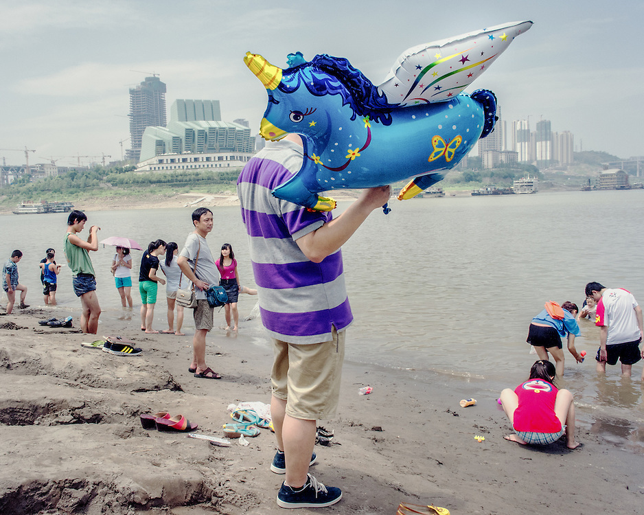 A man holding a balloon of a unicorn at the Chaotianmen dock, a meeting point of the Yantze and Jialing Rivers and a popular hangout to escape the heat in Chongqing.