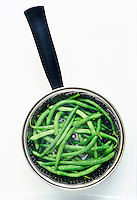 Greenbeans being steamed in a pan on the stove-top.