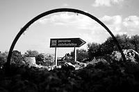 Reportage sul comune di Alessano per il progetto propugliaphoto..Segnaletica verticale di un percorso cicloturistico in conubio con un cerchio arruginito di una bicicletta..Macurano è un villaggio rupestre considerato un luogo di scambio e commercio, simbolo della cultura dell'olio per la presenza ad oggi di alcune tracce nelle grotte e di frantoi funzionanti nella zona. L'insediamento è caratterizzato da una serie di grotte sia naturali che scavate nel calcare, cisterne per la raccolta dell'acqua, sistemi di canalizzazione che scendono da Montesardo, viottoli, scalette e vie più larghe con antiche tracce di carri..Si ritiene che in questo sito, un vero e proprio centro abitato ben organizzato distante circa quattro km dalla costa, i monaci basiliani scappati dall'oriente in seguito alla lotta iconoclasta, trovarono rifugio e si dedicarono all'agricoltura..L'area del villaggio rupestre fu sicuramente sfruttata in epoche successive, lo prova l'esistenza di ben tre masserie di cui una fortificata e i resti di una serie di costruzioni che fanno parte dei numerosi esempi di architettura rurale presenti in questo territorio. .Il complesso masserizio, denominato Macurano, edificato probabilmente nel Cinquecento include la Masseria di Santa Lucia e la cappella di Santo Stefano. La Masseria è dominata dal nucleo originario, ovvero dalla torre cinquecentesca coronata da beccatelli a sostegno del parapetto aggettante del terrazzo sommitale.