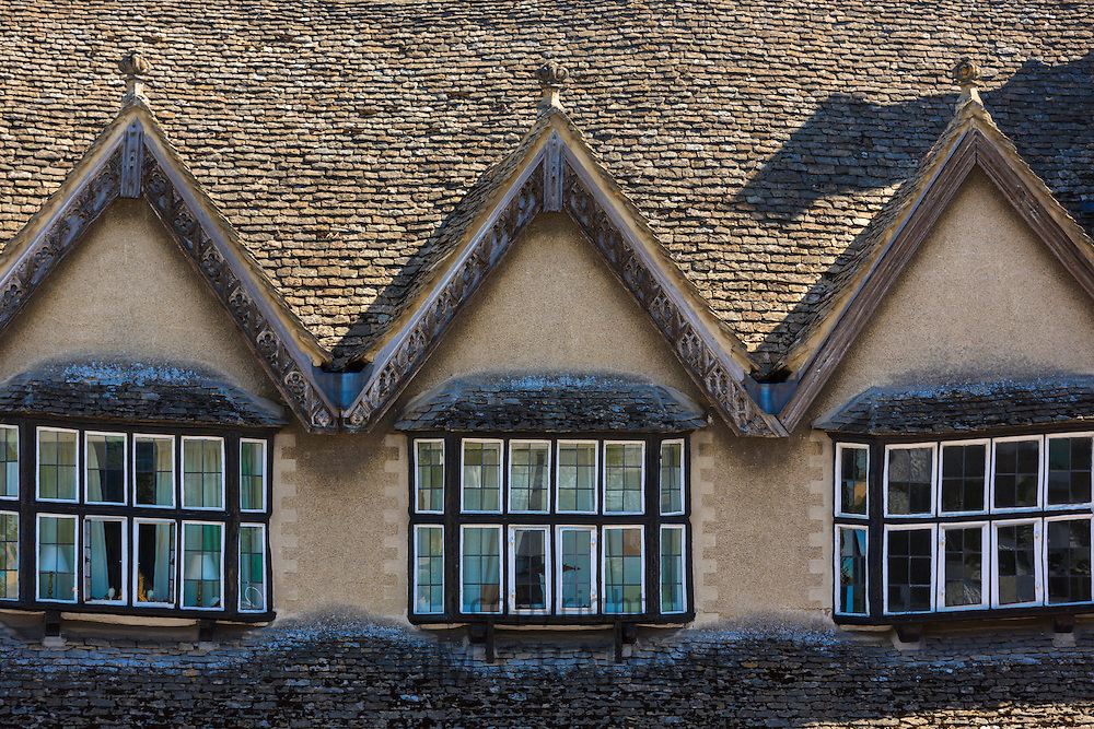 Medieval architecture windows and rooves of sloping old buildings along Burford High Street, The Cotswolds, Oxfordshire, UK