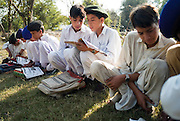 Young boys sit in the open grass areas in the grounds of their destroyed Nazarabad Government Boys School in SWAT....Some pupils have returned to the makeshift open-air class rooms whilst others still fear the return of the Taliban and choose to stay away from lessons. .