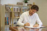 Leonhard Pfeifer, furniture designer, in his Hackney studio, London. His desk is the Proteus dining table, bespoke production, manufactured in the UK. Behind is the Newbury room divider manufactured in Estonia by Woodman.<br /> CREDIT: Vanessa Berberian for The Wall Street Journal<br /> GURU-Pfeifer