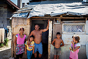 """Roma settlement Ostrovany. Marian with his family in front of their house located at the Roma settlement  Ostrovany in East Slovakia. Marian: """"We are devided (by the fence) - into white and the gypsies. When there was no fence some of the people stole just some fruits and vegetables. The """"Berlin Wall"""" does not matter for us anymore, standing there already a few years. They were building it well."""" In 2010, the town of Ostrovany received international media attention when the town council built a wall dividing private gardens and the neighboring Roma settlement. Several media outlets compared the look of Ostrovany's 150 m long wall with the Berlin Wall. Mayor Mr. Rehak sees the building as a """"fence"""" and not a wall."""