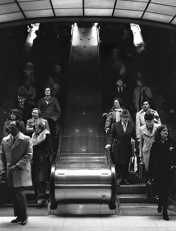 Elevators from the PanAm Building (now MetLife) to Grand Central Station concourse, trains, subways, busses, and the street. Rush hour crowd. Faces and postures tell many stories. 1975. Time of financial crisis in New York.