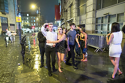 "© Licensed to London News Pictures . 23/12/2017. Manchester, UK. A man wearing a crown walks with a woman along Withy Grove , outside the Printworks . Revellers out in Manchester City Centre overnight during "" Mad Friday "" , named for being one of the busiest nights of the year for the emergency services in the UK . Photo credit: Joel Goodman/LNP"