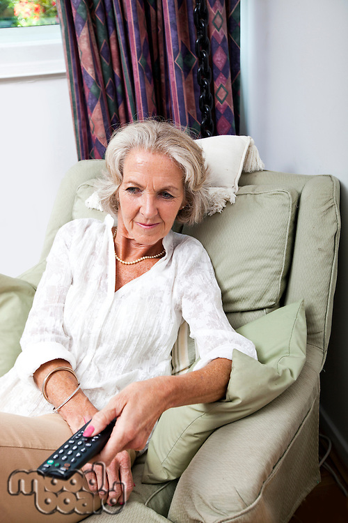 Senior woman changing channels with remote control on armchair at home