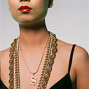 An Asian woman in black bra with rap-star gold chains including a dollar sign. (photo:Ann Summa).