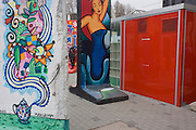 "Colourfully-painted sections of the old Berlin Wall are exhibited by local artists opposite the former Checkpoint Charlie, the former border between Communist East and West Berlin during the Cold War. The Berlin Wall was a barrier constructed by the German Democratic Republic (GDR, East Germany) starting on 13 August 1961, that completely cut off (by land) West Berlin from surrounding East Germany and from East Berlin. The Eastern Bloc claimed that the wall was erected to protect its population from fascist elements conspiring to prevent the ""will of the people"" in building a socialist state in East Germany. In practice, the Wall served to prevent the massive emigration and defection that marked Germany and the communist Eastern Bloc during the post-World War II period."