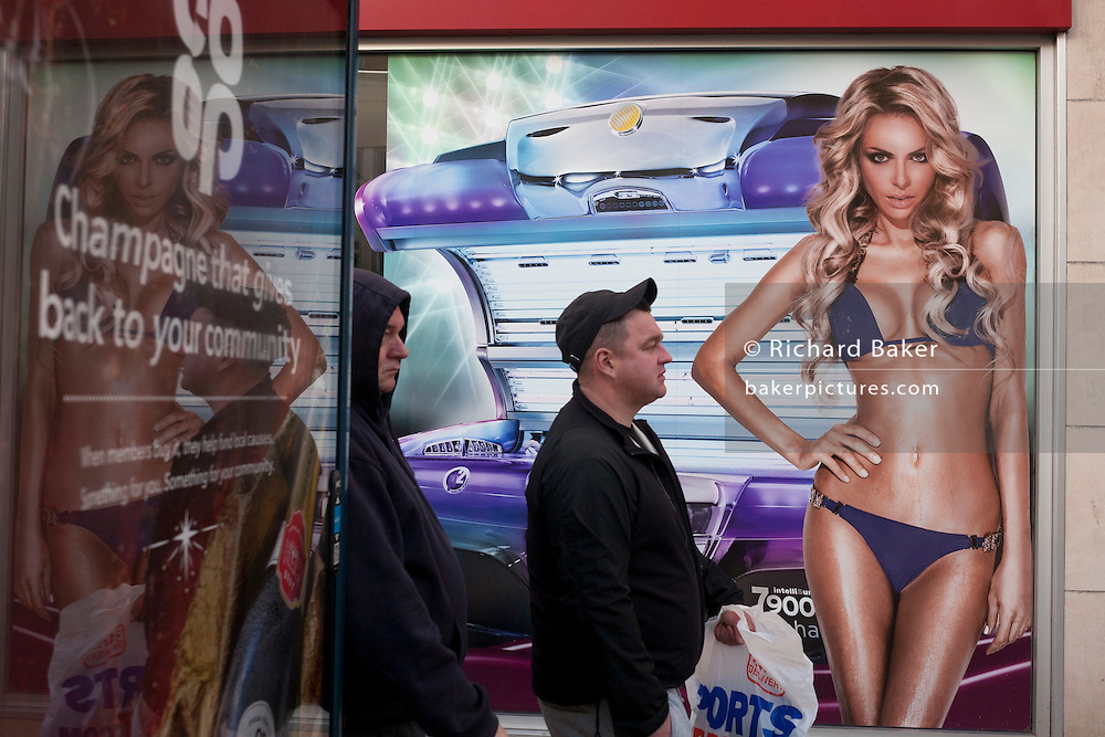 Two men walk past a girl wearing a bikini in a high-street advert for sunbeds, on 26th December 2016, in Bristol's Broadmead, England UK
