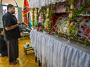 03 NOVEMBER 2014 - YANGON, MYANMAR: A man in Punja Mosque prays at a shrine representing Hussein bin Ali's coffin. Shia Muslims in Yangon started the celebration of Ashura Monday. Ashura commemorates the death of Hussein ibn Ali, the grandson of the Prophet Muhammed, in the 7th century. Hussein ibn Ali is considered by Shia Muslims to be the third Imam and the rightful successor of Muhammed. He was killed at the Battle of Karbala in 610 CE on the 10th day of Muharram, the first month of the Islamic calendar. According to Myanmar government statistics, only about 4% of Myanmar is Muslim. Many Muslims have fled Myanmar in recent years because of violence directed against Burmese Muslims by Buddhist nationalists.    PHOTO BY JACK KURTZ