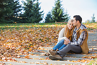 Loving couple hugging while sitting on steps in park during autumn