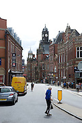 A frail elderly woman with grey hair using a walking stick and carrying a  bag, crosses Cliffird Street in York, UK.