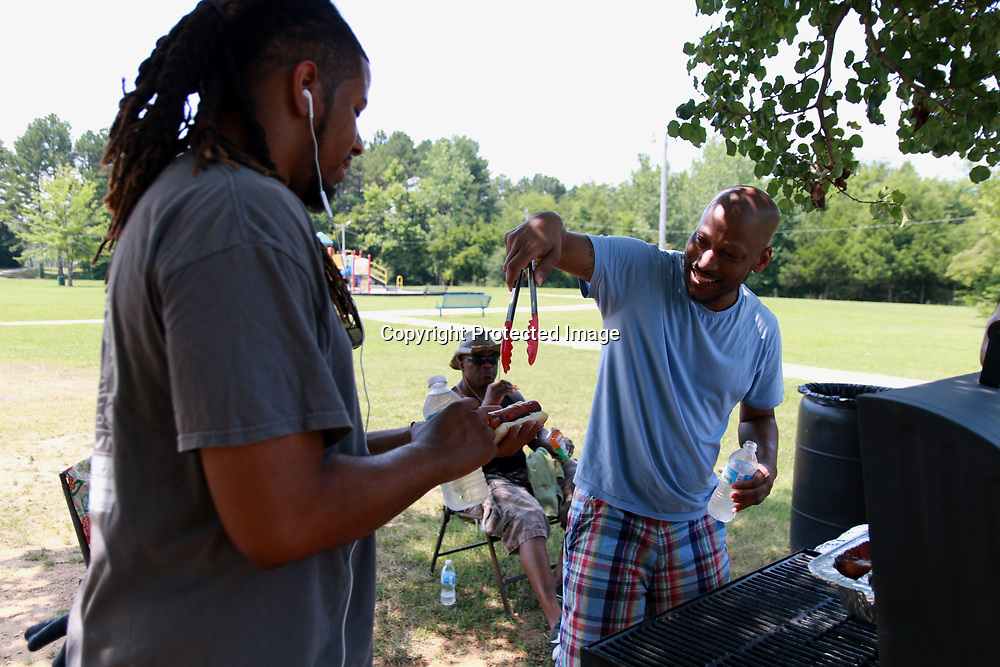 Bernard Judion serves up a freshly grilled hotdog to Ronnie Agnew at the Love More Hate Never community prayer gathering at Theron Nickols park Saturday.