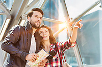 Portrait of young attractive couple looking on the map in the middle of the city with lens flare in background