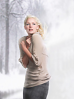 Woman with hair blowing arms crossed side view