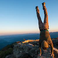 Sunrise at the top of Craggy Pinnacle Trail along the Blue Ridge Parkway northeast of Asheville, North Carolina. A local transplant (model released) practices a handstand during the first sunrise he has watched since moving to Asheville four years ago.