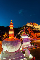 The Potala Palace with stupas in the foreground illuminated at twilight, Lhasa, Tibet (Xizang), China.