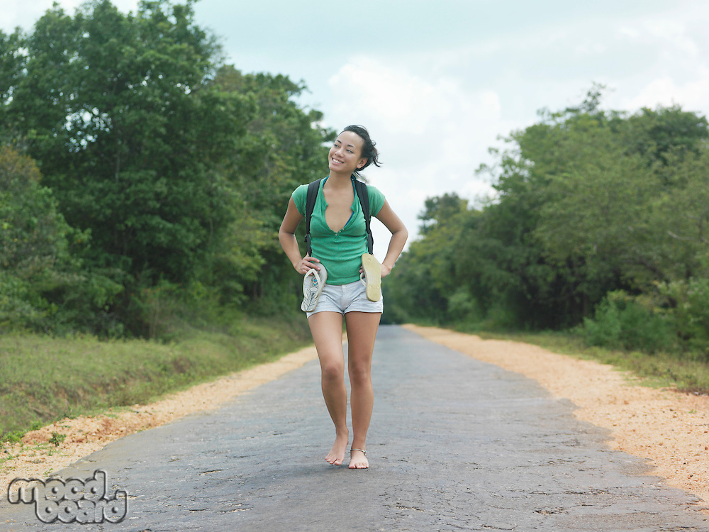 Young woman barefoot walking rural road smiling