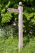 Wooden footpath sign directing walkers to a public footpath in Swinbrook, the Cotswolds, Oxfordshire, UK