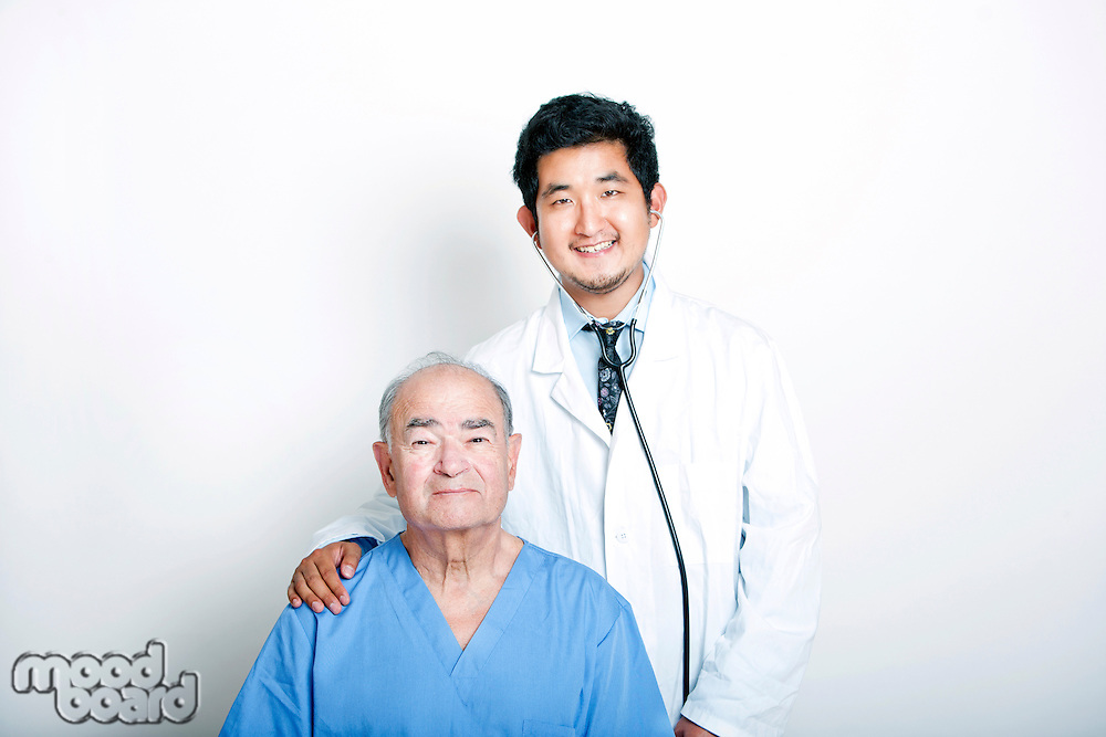 A young Asian Doctor with his hand on the shoulder of a Senior adult patient