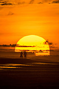 A couple stand on the beach silhouetted by the rising sun on a cloudy morning June 5, 2017 in Folly Beach, South Carolina. Folly Beach is a quirky beach community outside Charleston known to locals as the Edge of America.