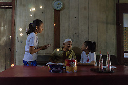 May 1st, 2014  - Sumber Sari Village, Indonesia. Devita (16) talks with her grandfather and cousin. Since her mother left the village to work in Singapore 3 years ago, she has been living with her grandparents together with her sister, Ika (18). © Thomas Cristofoletti / Ruom