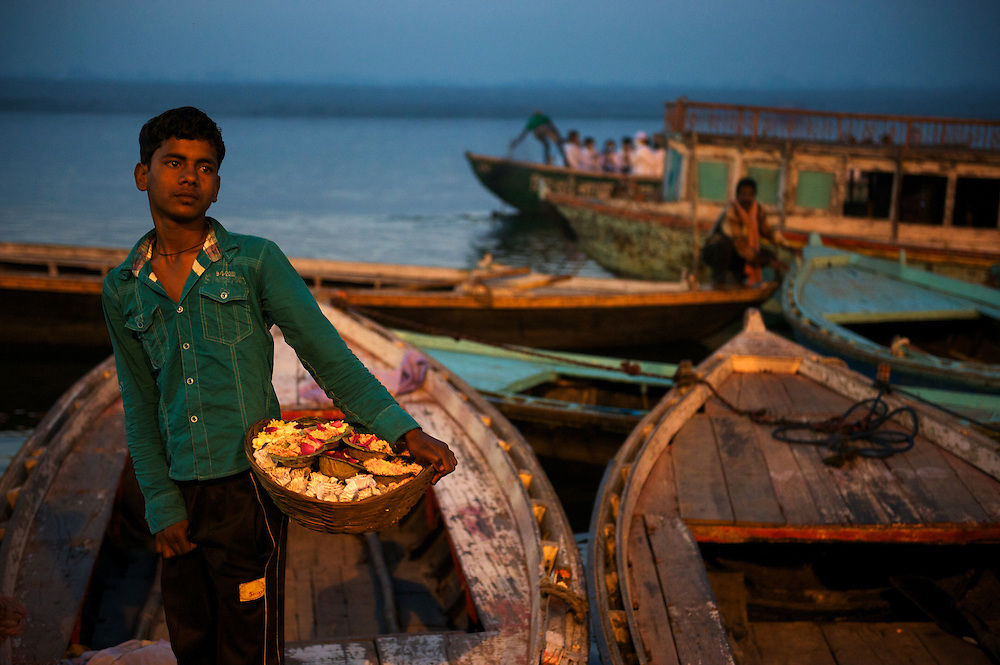 Indian boy selling flowers for puja, at dawn on the ganges.Varanasi, Uttar Pradesh, India