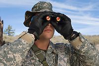 Soldier looking through binoculars, close-up